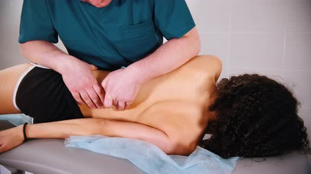 調整する : Chiropractic treatment - woman lying on her side and the doctor pushing her body to exercise the spine