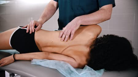 ajustando : Chiropractic treatment - woman lying on her side and the doctor pushing her body to straighten the vertebrae