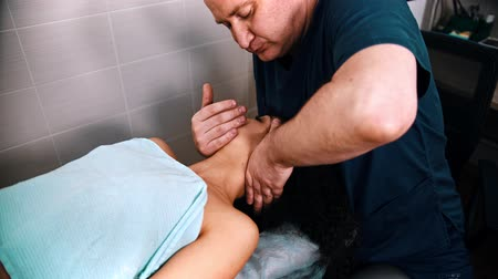 acupressure : Chiropractic treatment - the doctor specialist giving a woman patient a relaxing neck massage - bending the neck to the side