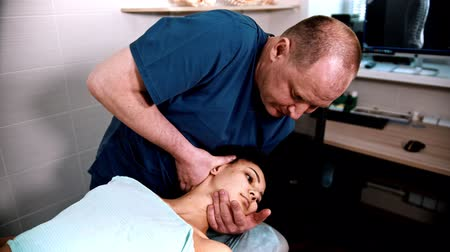 chiropraxie : Chiropractic treatment - the doctor specialist giving a woman patient a gentle neck massage - bending the neck to the sides