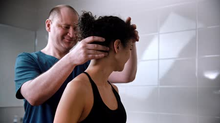 akupresura : Chiropractic treatment - the doctor twirls the young womans neck to the sides