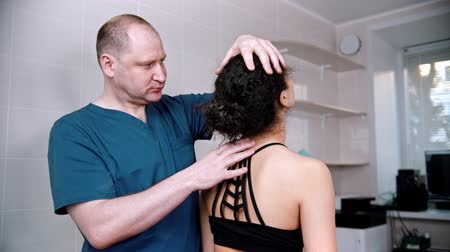 akupresura : Chiropractic treatment - the doctor inspecting the young woman before the session - bending the neck up and down and to the sides