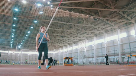 feminity : pole vaulting - young sportswoman is configuring to jump with a pole and running