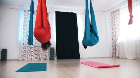 hamak : Aerial yoga - two women doing a spin and getting in the hammock