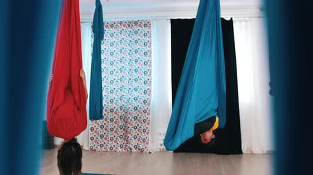posição : Aerial yoga - Two women digging in hammocks and hanging upside down