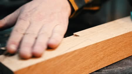 便利屋 : Carpentry industry - a man woodworker cutting out the recess on the wooden detail with a chisel