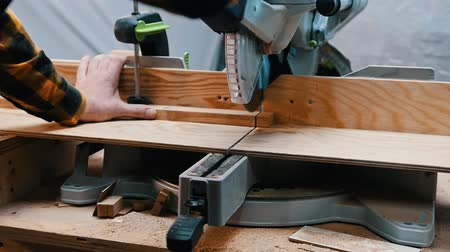 便利屋 : Carpentry industry - a woodworker cutting a piece of wood with a big circular saw in a workshop 動画素材