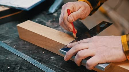 плотничные работы : Carpentry industry - a man woodworker making marks for cutting on the wooden detail with a pencil