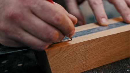 便利屋 : Carpentry industry - a woodworker measuring the wooden piece with a yardstick and making marks with a pencil 動画素材