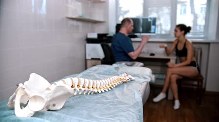 調整する : Chiropractic treatment - the doctor inspecting the young woman before the session - model of the human spine placed on the couch