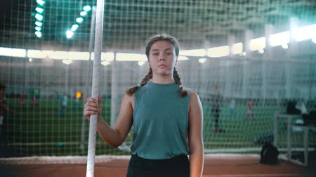 participante : pole vaulting - young woman is standing with a pole in hands