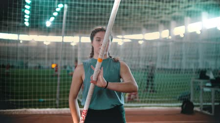 participante : pole vaulting - young woman raised a pole in hands