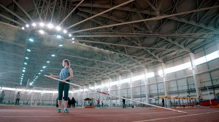 feminity : pole vaulting - the sportswoman is taking a long pole and running Stock Footage