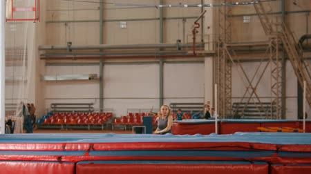feminity : pole vaulting - young sportswoman is running and jumping over the bar