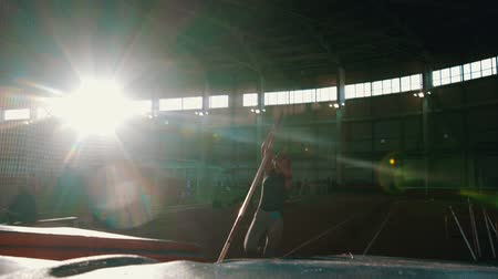 participants : pole vaulting - young woman is running and jumping over the bar