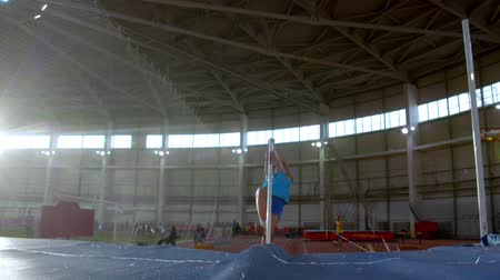 participante : pole vaulting - young guy in blue t shirt is running and jumping over the bar