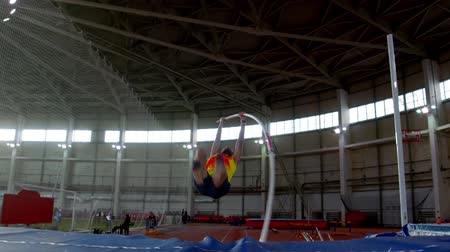 participante : pole vaulting - sportsman in yellow t shirt is running and jumping over the bar