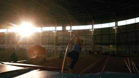 feminity : pole vaulting - young and beautiful athlete in gray t shirt is running and jumping over the bar