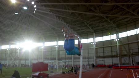 résztvevő : pole vaulting - young sportsman in blue t shirt is running and jumping over the bar