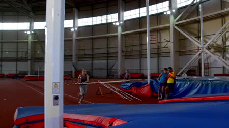 feminity : pole vaulting - young and beautiful sportswoman in gray t shirt is running jumping over the bar