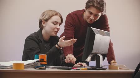 damga : office - a man is helping to a woman deal with a computer