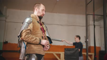 İskandinav : A man putting on a knight armour - putting on a jacket