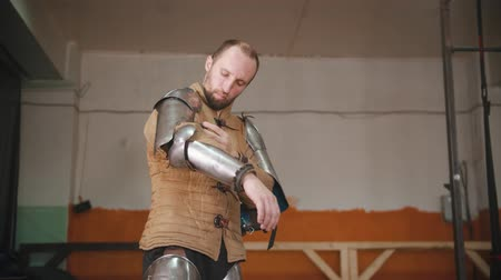 rytíř : A man putting on a knight armour - putting on full armor for the training