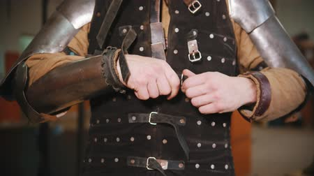 İskandinav : Men putting on a knight armour in the dressing room - putting on a jacket