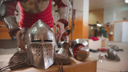 İskandinav : A man in the dressing room putting on the armour helmet Stok Video