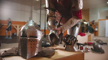 İskandinav : A man in the dressing room putting on the armour iron gloves