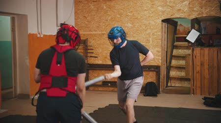escandinavo : Two men knightes having a training fight in the gym using a safe sword