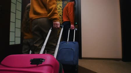 chegada : A young family entering a hotel room - dragging their luggage after them
