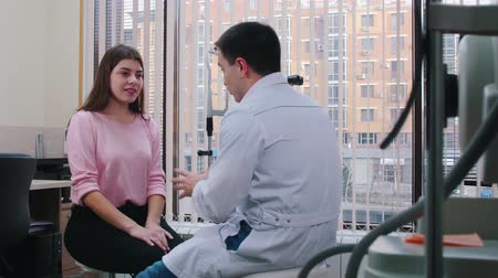 eyepieces : Ophthalmology treatment - young woman having a consultation with an optometry doctor in the bright cabinet - listening what the doctor says Stock Footage
