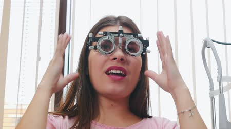 optyk : Ophthalmology treatment - a young woman putting on an optometry device for vision test