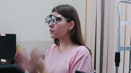 eyepieces : Ophthalmology treatment - a young woman putting on an optometry device for vision test with lenses - smiling and talking with a doctor
