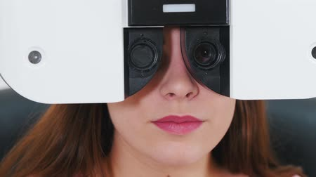 eyepieces : Ophthalmology treatment - a young woman checking her visual acuity with a special optometry equipment - a machine changing lenses