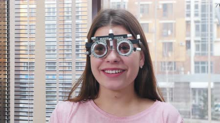 eyepieces : Ophthalmology treatment - a young smiling woman sitting in the optometry device for vision test