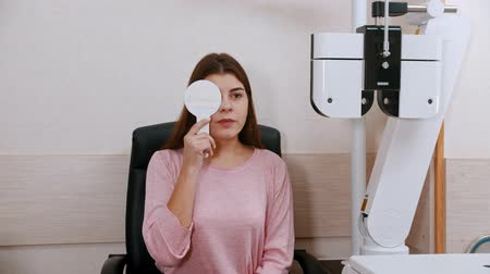 eyepieces : Ophthalmology treatment - young woman checking her visual acuity - closing an eye and reading letters