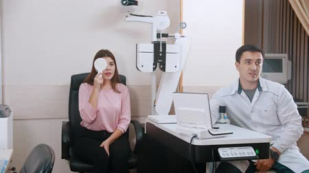 eyepieces : Ophthalmology treatment - young woman checking her visual acuity - closing an eye and reading letters - a doctor sitting near and switching the screen
