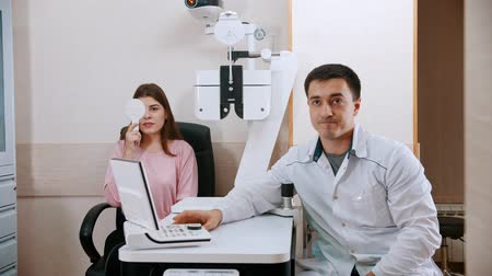eyepieces : Ophthalmology treatment - young woman checking her visual acuity - - a doctor sitting near by her