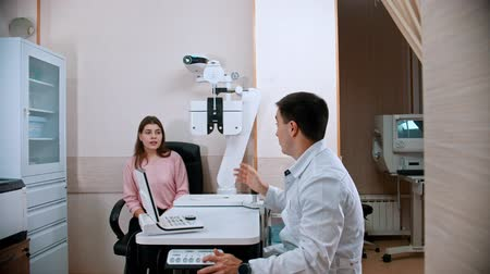 eyepieces : Ophthalmology treatment - young smiling woman checking her visual acuity on an optometric equipment with a doctor