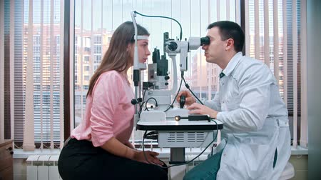 eyepieces : Ophthalmology treatment - young pretty woman checking her visual acuity with a special equipment in the spacious cabinet on the background of the panoramic window