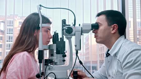 диагностировать : Ophthalmology treatment - a doctor checking young womans visual acuity with a special equipment using the light - a spacious cabinet on the background of the panoramic window Стоковые видеозаписи