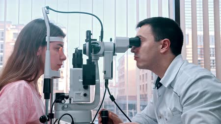 eyepieces : Ophthalmology treatment - a doctor checking young womans visual acuity with a special equipment using the light - a spacious cabinet with panoramic window Stock Footage