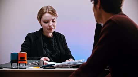 descarga : An office working - a man comes to a woman and giving her a document - a woman pulls out a nameplate with YOURE FIRED sign