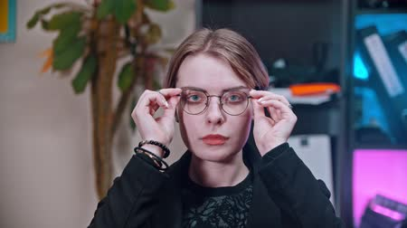объяснять : A business woman putting on glasses - sitting in the office Стоковые видеозаписи
