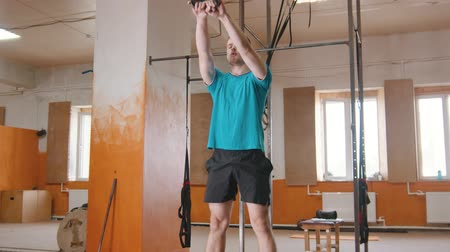 sollevamento pesi : Sports training indoors - a handsome man squatting with a weight in his hands Filmati Stock