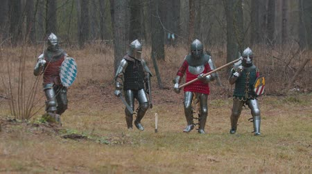броня : Four men knightes walking in the row in the forest in full armour
