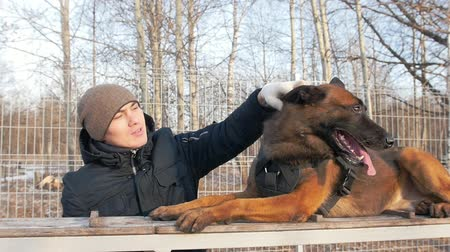 trained : A dog and his trainer on the playground - petting the dog