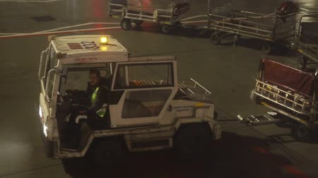 via aerea : 23-11-2019 NETHERLANDS, AMSTERDAM: An airport staff prepare the transportation for the baggage